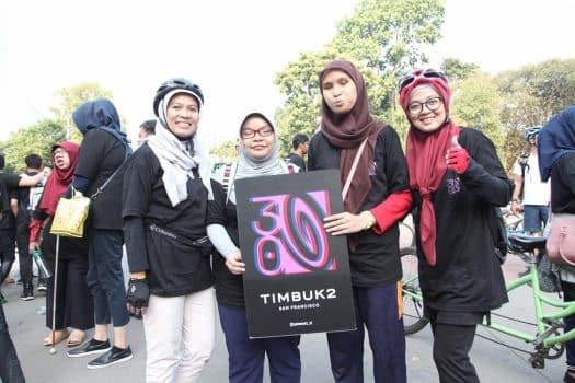 Beberapa orang memegang banner logo 30 tahun Timbuk 2