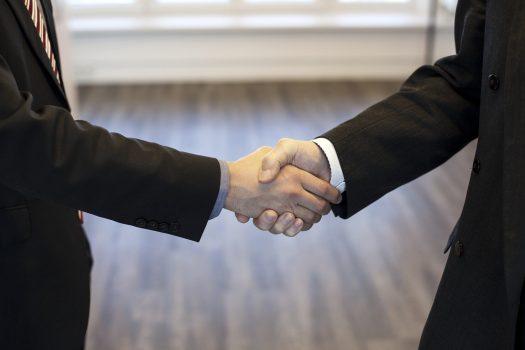 dua tangan mengenakan jas formal saling menjabat