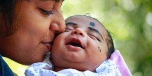 seorang ibu mencium pipi bayinya