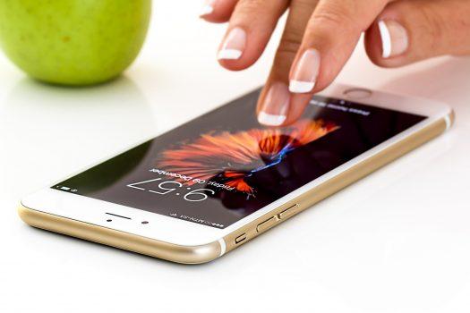 smart phone layar sentuh di atas meja sedang disentuh layarnya dengan jari seseorang