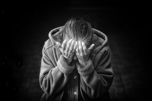 seorang perempuan menunduk dan menutup wajah dengan kedua tangan, tampak depresi