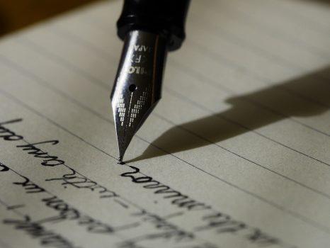 ujung pena dengan bercak tinta di atas kertas putih