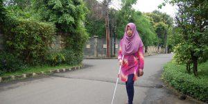 tunanetra berjalan sendirian dengan tongkatnya. Background suasana perumahan