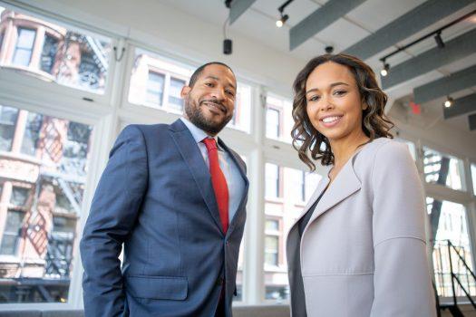 pria dan wanita berpakaian formal berdiri di depan sebuah gedung